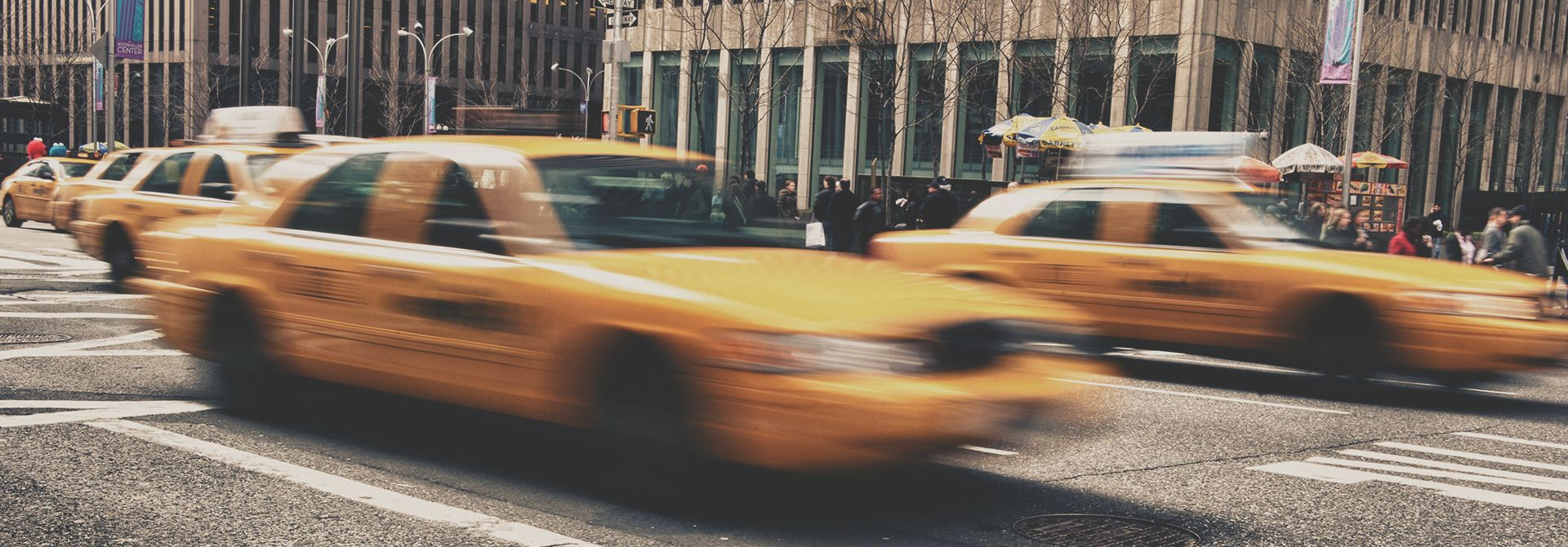 taxis driving down a new york street